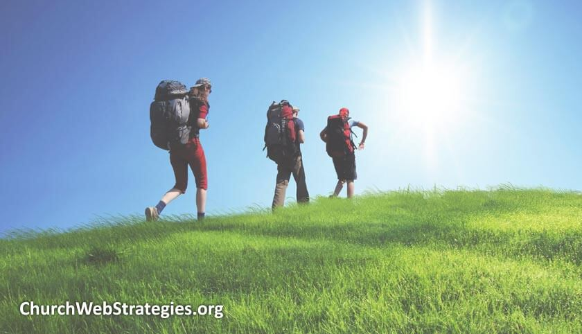 Hikers walking up a grassy hill