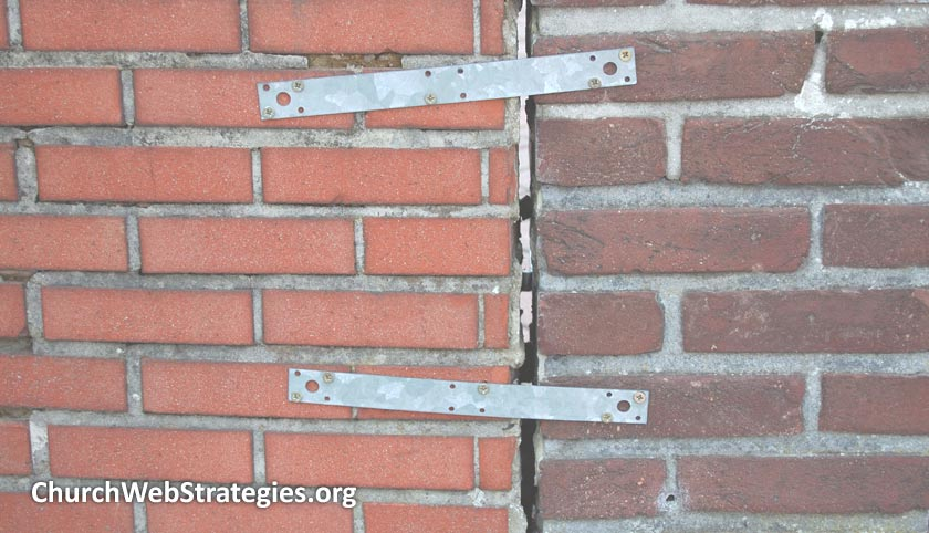 two brick walls held together with metal bars