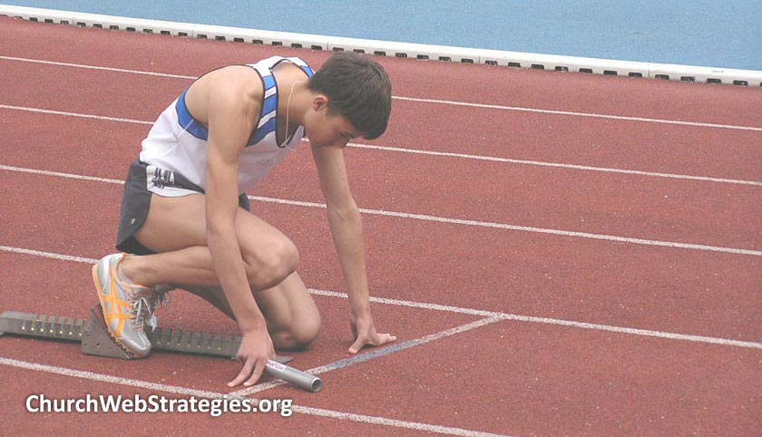 man crouched down at race start line